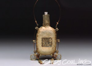 High fired, hand built clay bottle. Stamp design carved by the artist. Copper wire and beads are used to decorate.